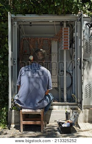ATHENS GREECE - AUGUST 1 2017: Telephone technician repairs wire connections in network switchboard exchange box.