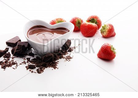 Chocolate fondue melted with fresh strawberries and milk chocolate pieces