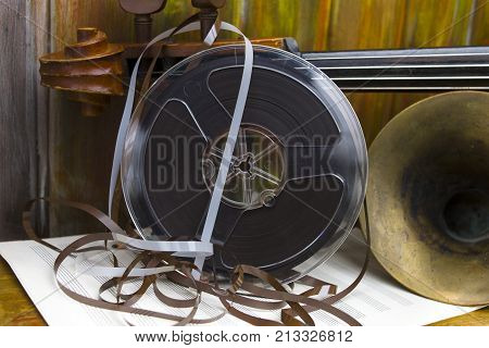 Reel to reel tape next to the trumpet and old cello