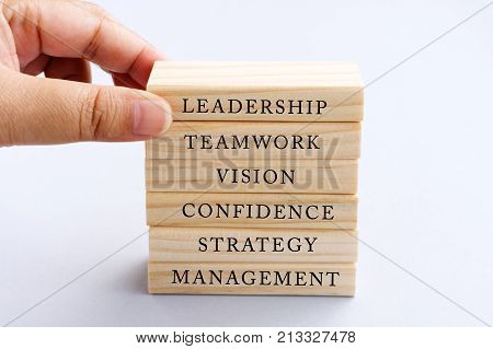 Hand Picking Wood Block with Word Leadership. Business Concept - Wood Top Block with Word: Leadership Teamwork Vision Confidence Strategy and Management.