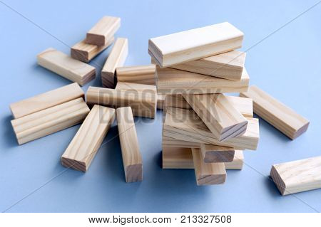 Business Concept, Building A Business. Stacked And Collapsed On Wood Blocks.
