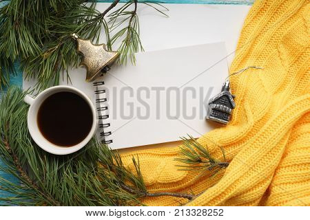 Christmas background with a Cup  of coffee, a notebook, Christmas toys, branches of pine with large needles and a yellow sweater. Top view, close-up