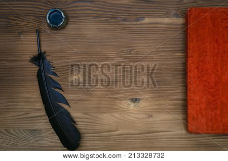 Closed vintage book with blank paper page black feather pen and inkwell on table background. Education background with copy space. Writer desk table.