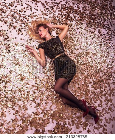 Happy blonde woman lies on floor in confetti everywhere. New year and holliday concept