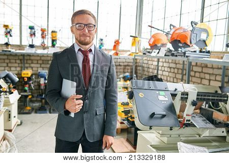 Portrait of successful salesman wearing suit posing looking at camera, standing by machine tools in industrial  showroom