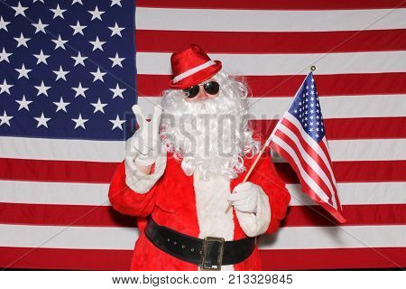Santa Claus stands in front of the American Flag.  Santa Claus Smiles and Poses in front of an American Flag.