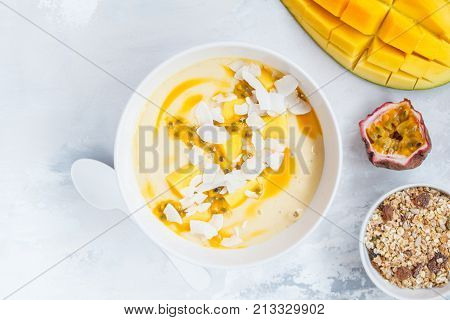 Mango smoothie bowl with coconut granola and passion fruit. Healthy vegan diet breakfast concept.
