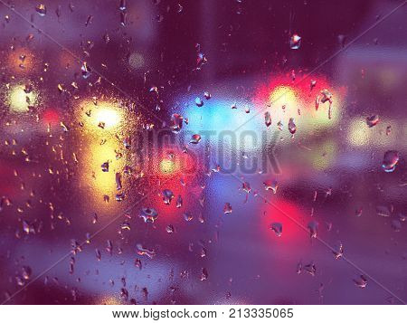 Drops of water during the rain in a city. Rain drops cover the window glass, a blurred city lights are on the background. Lights of different colors.