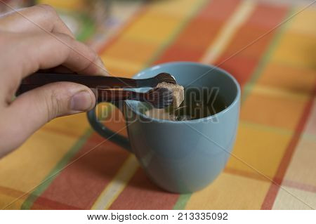 Lump Sugar With Tongs Putting In A Cup Of Tea