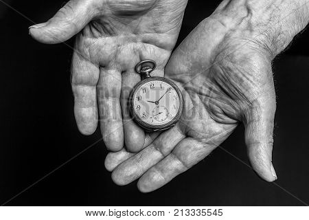 Time concept. Vintage clock in old senior wrinkled male hands on black background.