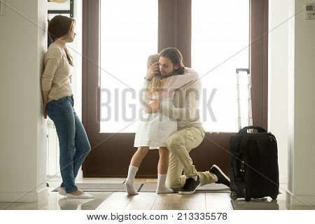Sad father hugging little daughter before leaving for long business trip, upset dad embracing crying girl saying goodbye to daddy at home in hall with baggage, family separation, good bye, farewell