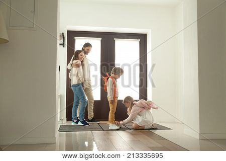 Little sister helping brother to tie shoes, girl fasten shoelaces of boy while parents looking at kids siblings son and daughter helping getting ready for walk together standing in hallway at home