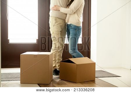 Couple embracing standing near cardboard boxes with belongings, happy homeowners just moved in own house apartment, family moving into new home concept, mortgage loan, close up view