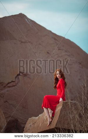 portrait of a beautiful young girl with red hair in a red tight dress near the lake shore