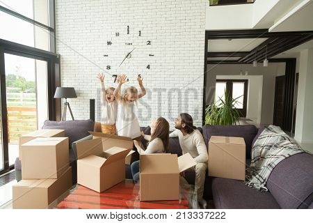 Happy married couple with kids playing while packing unpacking in modern living room interior, cheerful family and children having fun with boxes on couch together at moving day, move in out new home