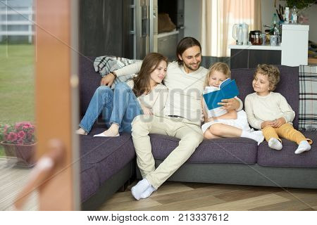 Happy family with kids holding book sitting on sofa, father embracing mother reading fairytale to children relaxing on couch, parents and son daughter having fun with storybook at home, story time