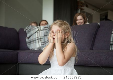 Little girl closing eyes covering face with hands playing hide and seek game with parents and brother hiding behind sofa peeking out in living room, happy family having fun together with kids at home