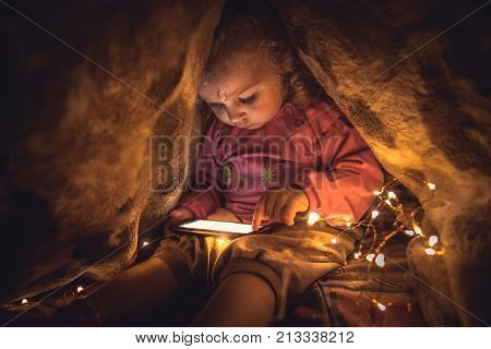 Curious child playing with smart phone hiding in secret place