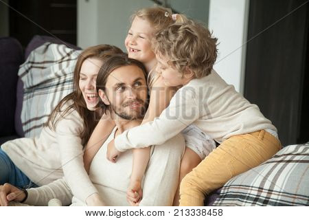 Happy parents and little children laughing having fun sitting on sofa, kids and wife hugging husband dad on couch, cozy loving family of four at home together, congratulating daddy with fathers day