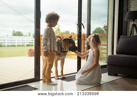Children caressing watch dog protecting home, kids playing with big pet coming inside house, little boy and girl having fun stroking german shepherd standing at door, leisure with domestic animal