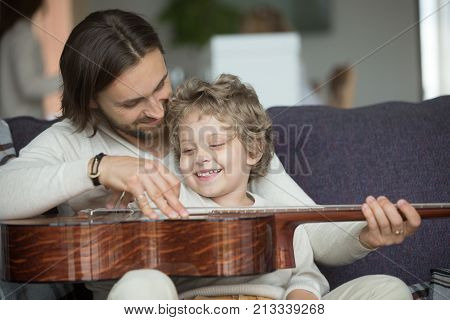 Young father teaching little son to play musical instrument at home, loving dad strumming guitar with small boy, parent and child relaxing on sofa, family leisure music activity, musically gifted kid