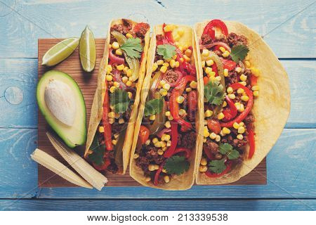 Mexican tacos with minced beef, vegetables and salsa. Tacos al pastor on wooden blue rustic background. Top view.