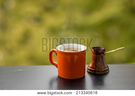 Hot tasty steaming coffee brewed in traditional turkish coffee pot and sugar, cafe wooden table outdoors, autumn background