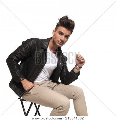 cool guy with nice hair style is sitting on a chair on white background; he wears casual clothes and a leather jacket