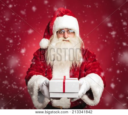 happy santa claus offering a present to all the good kids on red background
