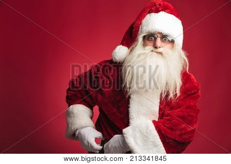 santa claus fixing his belt on red background
