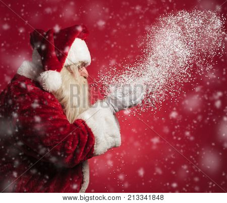 santa claus blowing snow from his hands on red background, side view image