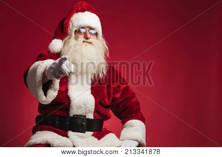 seated santa claus pointing his finger on red studio background