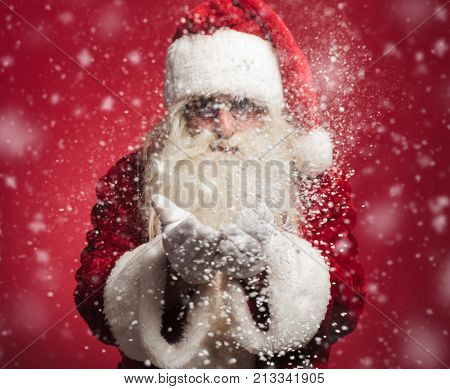 santa claus blowing snow flakes out of his hands at the camera on red background