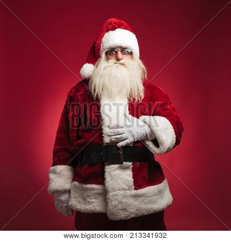 hungry santa claus with palm on his belly standing on red background