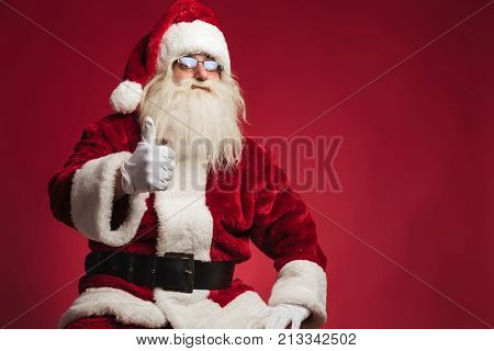 seated santa claus making the ok thumbs up sign on red background