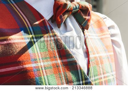 closeup of matching tartan bowtie and waistcoat outdoors in the warm sunlight with a white shirt menswear clothing