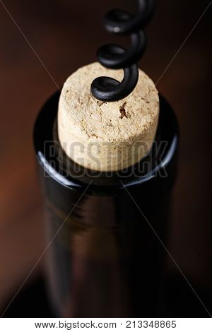 a bottle of wine is opened with a corkscrew, a corkscrew is screwed into a bottle stopper