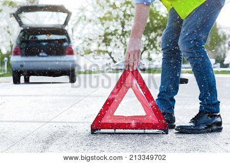 Man Placing A Reflective Red Triangle