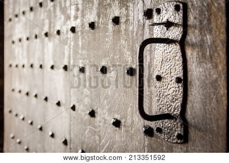 Heavy old wooden castle door with studs. Soft focus and backlit. Stirling Castle Scotland