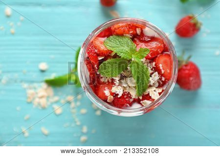 Delicious parfait with strawberry and oatmeal in glass jar on table