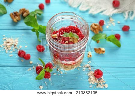Delicious parfait with raspberry and oatmeal in glass jar on table