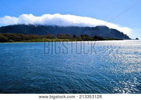 Estuary at the mouth of the Klamath River which is known for salmon fishing surrounded by mountains and fog taken at the Klamath River Basin in the rural Northern California Coast