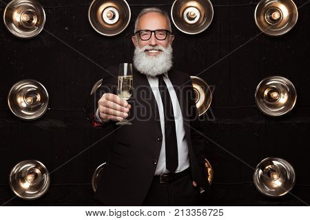 The mas drink for a girls. Happy bearded adult man drink a champagne and shows a glasses of champagne to camera. Toast for beautiful girl. Businessman celebrate a holiday.