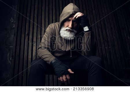 Serious bearded man ready to fight. Sport and fit man in hood thinking about future fight. Workout and box sport. Extreme sport for old man. Close up portrait of man hands over his sports bandages