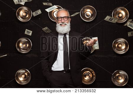 Portrait of happy rich business man which shows a gesture of money while banknotes of money fly behind. Rich white bearded man in a suit and fashion glasses