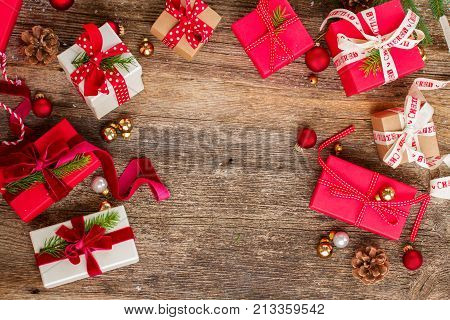 Christmas gift giving - pile of wrapped in red and white paper christmas gift boxes with open one on wooden background, flat lay frame with copy space