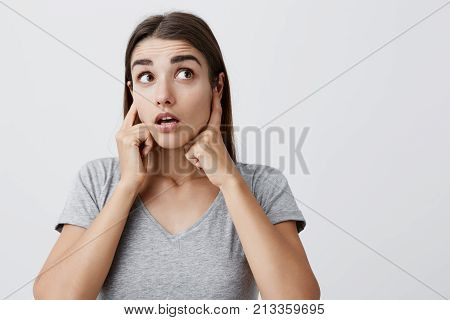 I don't hear anything. Body language. Close up of young attractive caucasian girl with long hair in casual gray t-shirt plugging ears with fingers, looking aside with raised eyebrows and surprised expression