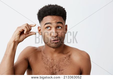 Portrait of funny dark-skinned american guy with curly hair and without clothes looking aside with silly and cynic expression, gesticulating with hand. People's emotions