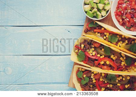 Mexican tacos with minced beef, vegetables and salsa. Tacos al pastor on wooden blue rustic background. Top view with copy space.