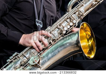The right hand of the musician in a black shirt rests on a saxophone-baritone. Close up.